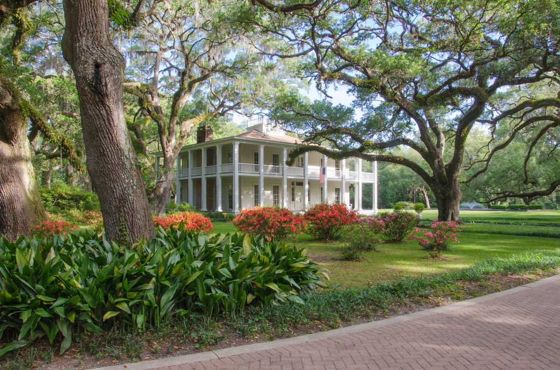 A view of the historic Wesley house in Eden Gardens State Park, Florida. Also showing azaleas bushes in bloom and live oak trees