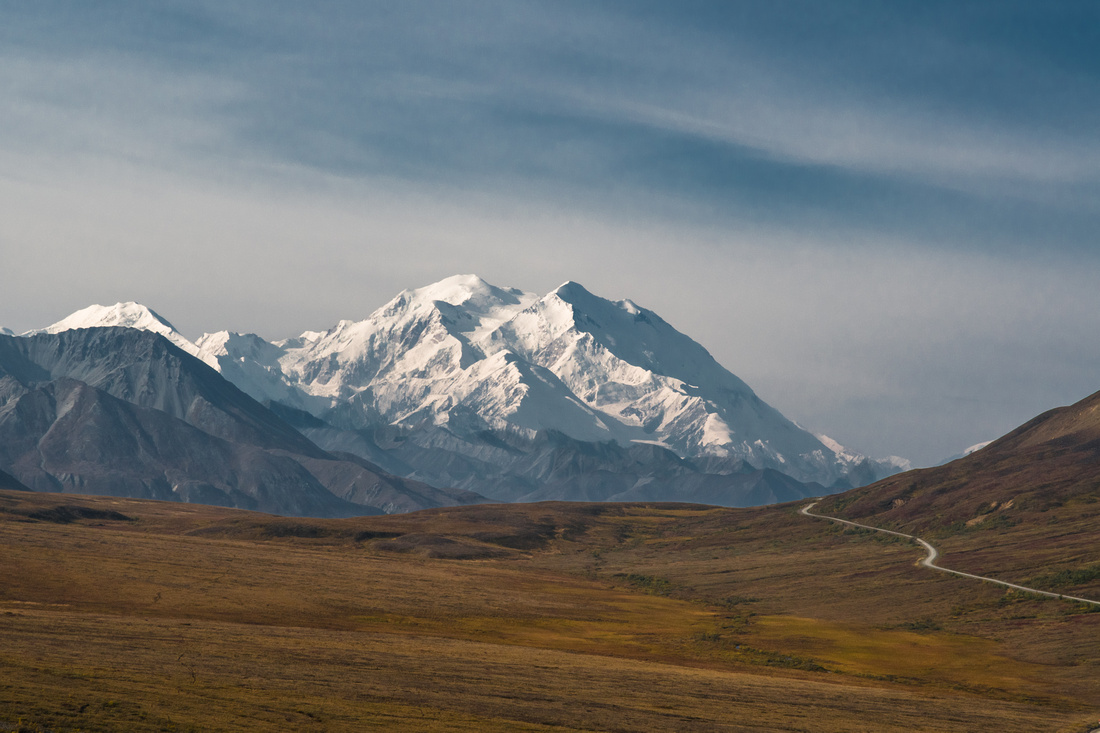 A gravel road through the autumn colored tundra vanishing into the mountains with Mount Denali-McKinley in the background copy