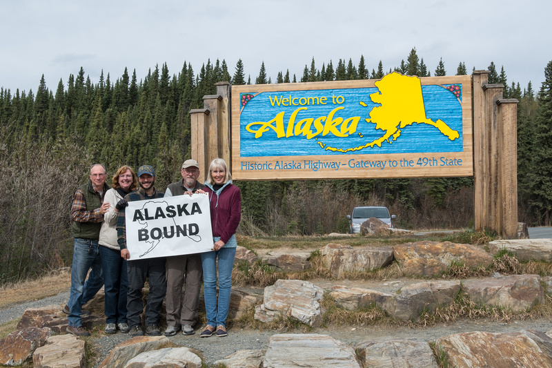 """A group of travelers posing at the """"Welcome to Alaska"""" sign at the Canadian-Alaska border"""