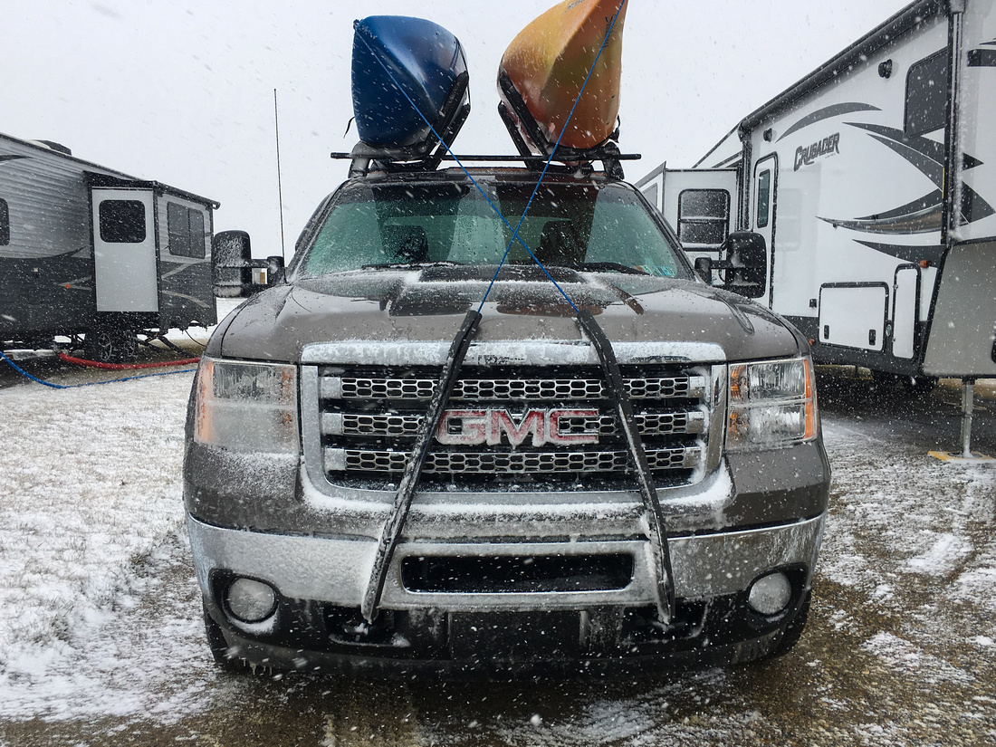 GMC truck with kayaks in front of RV's in a snow storm